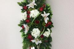 Dessus de cercueil roses rouges et fleurs blanches